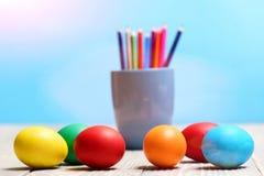 被绘的复活节彩蛋和五颜六色的铅笔在蓝色杯子设置了 免版税库存照片