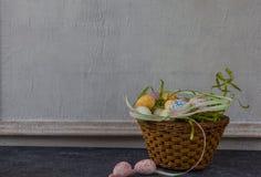 被绘的复活节彩蛋的构成在黑暗的石桌和葡萄酒白色墙壁背景的 库存照片
