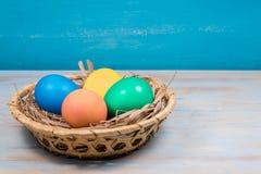 被绘的复活节彩蛋篮子在蓝色背景的与题字的一个地方 免版税图库摄影