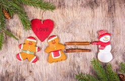 被绘的姜饼 与甜点的圣诞节装饰和在一个木板的冷杉分支 库存照片