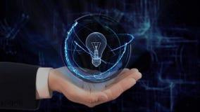 被绘的手显示概念全息图在他的手的电灯泡灯 股票录像