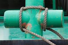 被绘的绿色十字形的系船柱和附加的大索 免版税库存图片