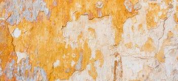 被绘的老破裂的被风化的破旧的黄色涂了灰泥被剥皮的墙壁横幅背景 免版税库存照片