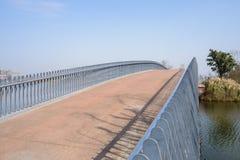 被绘的车行道和曲拱桥梁象肋骨的扶手栏杆在水的 库存图片