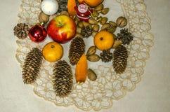 被绣的餐巾和圣诞礼物,发光的球,圣诞老人项目,苹果,柑桔,杏仁,与在胶合板的杉木锥体 库存图片
