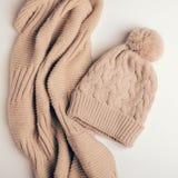 被编织的围巾一个管子或一个衣领从温暖的螺纹和米黄盖帽有绒球的 衣裳为秋天和冬天 特写镜头 免版税库存图片