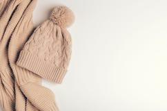 被编织的围巾一个管子或衣领从温暖的螺纹和一个米黄盖帽有绒球的 辅助部件为秋天和冬天 复制 库存照片