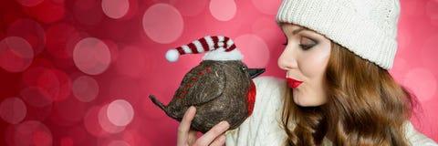 被编织的套头衫的华美的妇女和送亲吻到知更鸟圣诞节鸟的帽子 滑稽的xmas横幅 免版税库存图片