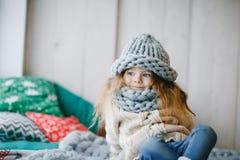 被编织的帽子和围巾的女婴 免版税库存照片
