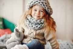 被编织的帽子和围巾的女婴 免版税图库摄影