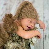 被编织的帽子和裤子的愉快的微笑的新出生的男婴,合理地 库存照片