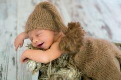 被编织的帽子和裤子的愉快的微笑的新出生的男婴,合理地 库存图片