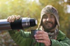 被编织的帽子的人,有微笑的倾吐一份热的饮料-茶或咖啡 免版税库存照片