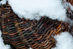 被编织的木篮子片断在白色雪的 图库摄影