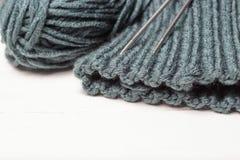 被编织的材料、编织针和丝球在白色背景,拷贝空间 免版税库存图片