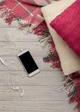 被编织的枕头、格子花呢披肩和智能手机在一轻的木backgrou 免版税库存照片