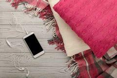 被编织的枕头、格子花呢披肩和智能手机在一轻的木backgrou 库存照片