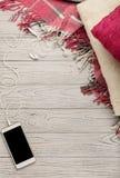 被编织的枕头、格子花呢披肩和智能手机在一轻的木backgrou 库存图片