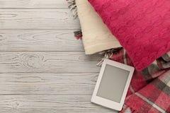 被编织的枕头、格子花呢披肩和eBook在轻的木背景 库存图片