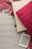 被编织的枕头、格子花呢披肩和eBook在轻的木背景 免版税库存图片