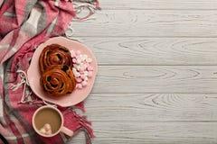 被编织的枕头和格子花呢披肩、小圆面包和咖啡在轻的木bac 库存图片