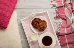 被编织的枕头和格子花呢披肩、小圆面包和咖啡在轻的木bac 免版税库存图片