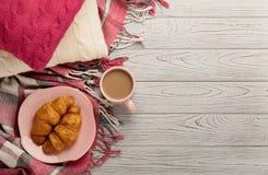 被编织的枕头和格子花呢披肩、新月形面包和咖啡在轻的木头 库存照片