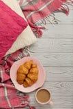 被编织的枕头和格子花呢披肩、新月形面包和咖啡在轻的木头 免版税库存照片