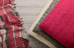 被编织的枕头和格子花呢披肩在轻的木背景 库存照片