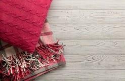 被编织的枕头和格子花呢披肩在轻的木背景 免版税库存图片