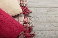 被编织的枕头和格子花呢披肩在轻的木背景 免版税库存照片