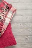 被编织的枕头和格子花呢披肩在轻的木背景 图库摄影