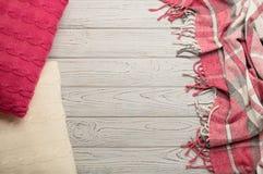 被编织的枕头和格子花呢披肩在轻的木背景 库存图片