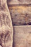 被编织的格子花呢披肩,在老木板的毛线衣 免版税库存照片