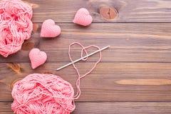 被编织的桃红色螺纹心脏、缠结和针 库存照片
