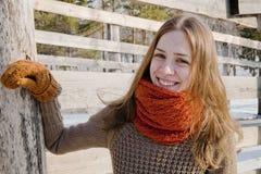 被编织的橙色围巾的女孩 免版税库存图片