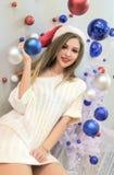 被编织的毛线衣和毛皮拖鞋的美丽的性感女孩微笑着 新的主题年 在白色的蓝色和红色圣诞节球 图库摄影