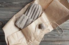 被编织的米黄帽子在与一个小样品的牛皮纸包装 免版税库存照片