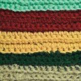 被编织的美好的羊毛服装五颜六色的条纹背景自然纹理,黄色,灰棕色,深紫红色,蓝色,绿色围巾宏指令特写镜头 免版税图库摄影