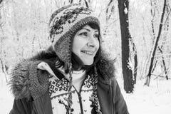 被编织的舒适穿戴的微笑的少女在黑白多雪的冬天的森林里 愉快的妇女画象冬天公园黑白照片的 图库摄影