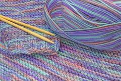 被编织的五颜六色的毛线衣、毛纱球和针 被编织的套头衫、温暖的冬天布料和混合物羊毛球  免版税库存照片