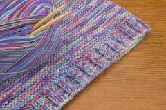 被编织的五颜六色的毛线衣、毛纱球和针 被编织的套头衫、温暖的冬天布料和混合物羊毛球  免版税图库摄影