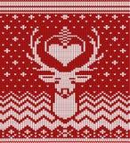 被编织的冬天鹿红色背景 库存图片