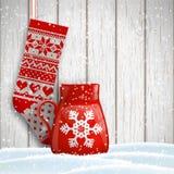 被编织的圣诞节长袜和红色用抽象白色雪花装饰的茶杯,例证 库存图片
