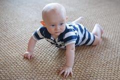 被编织的地毯的恼怒的爬行的婴孩 免版税库存图片