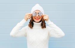 被编织的帽子和毛线衣的愉快的微笑的少妇有在获得的面孔的雪花的在蓝色背景的乐趣 库存图片