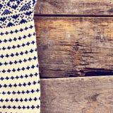 被编织的格子花呢披肩,在老木板的毛线衣 免版税图库摄影