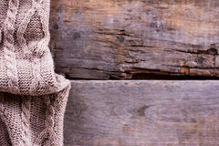 被编织的格子花呢披肩,在老木板的毛线衣 免版税库存图片