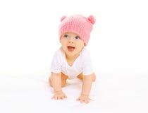 被编织的桃红色帽子的愉快的逗人喜爱的微笑的婴孩在白色爬行 免版税库存图片