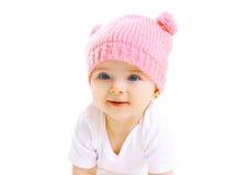 被编织的桃红色帽子的画象逗人喜爱的微笑的婴孩在白色 免版税库存图片